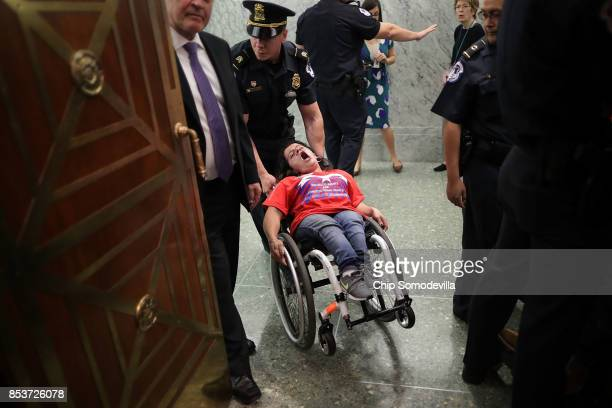 Capitol Police remove a protester in a wheel chair from a Senate Finance Committee hearing about the proposed Graham-Cassidy Healthcare Bill in the...
