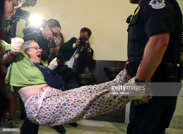 Capitol Police remove a woman from a protest in front of the office of Senate Majority Leader Mitch McConnell inside the Russell Senate Office...