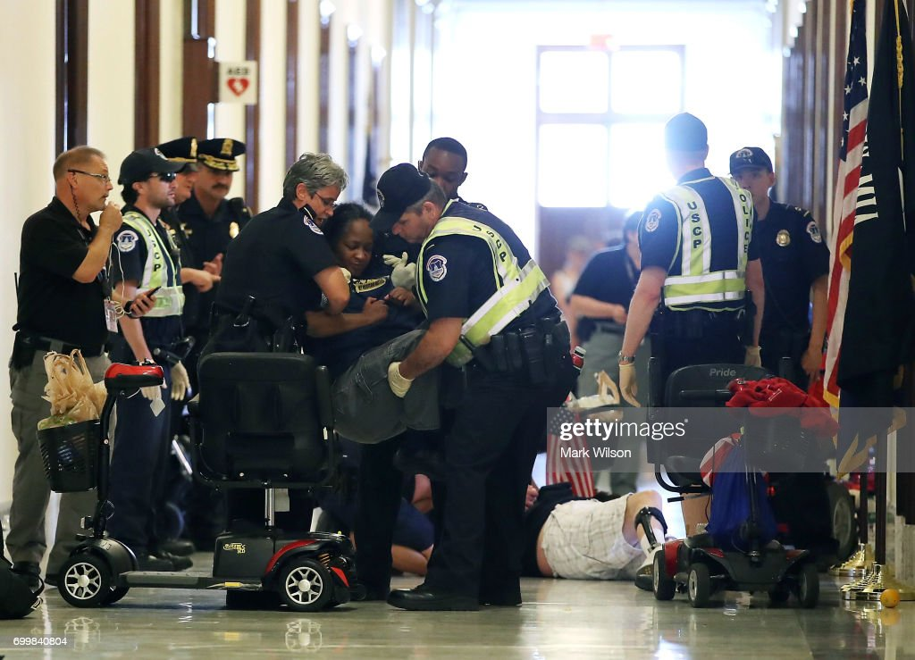 U.S. Capitol Police remove protesters from in front of the office of Senate Majority Leader Mitch McConnell (R-KY) inside the Russell Senate Office Building on Capitol Hill, on June 22, 2017 in Washington, DC. Members of a group with disabilities were protesting the proposed GOP health care plan that was unveiled today.
