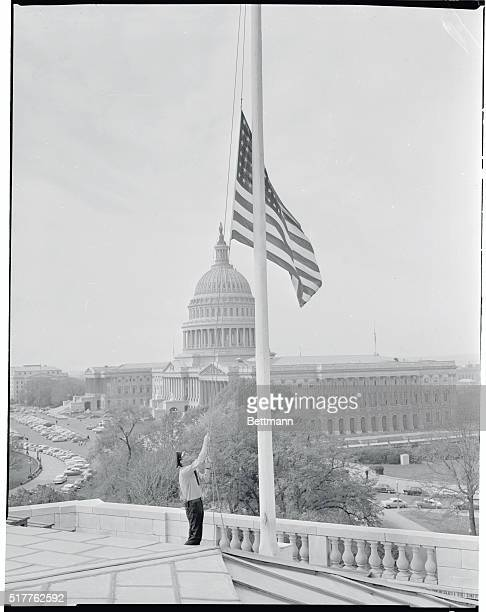 Capitol policeman James L Goodall lowers the flag atop the Senate office building to half staff in mourning for Senator Alben Barkley of Kentucky who...