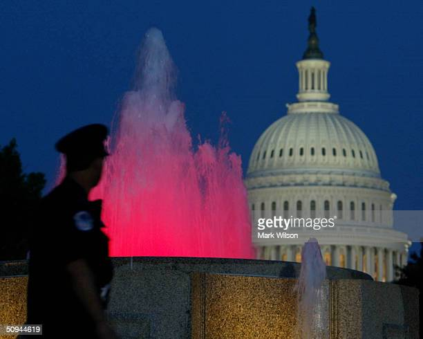 Capitol Policeman walks by a colored fountain near the Capitol June 9, 2004 in Washington, DC. Former President Ronald Reagan will lie in state in...