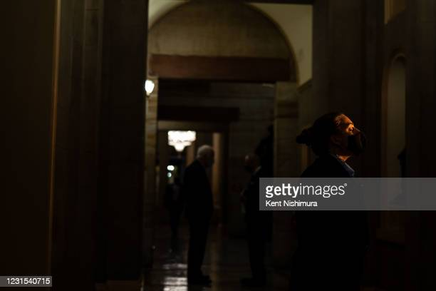 Capitol Security Detail member stands in a hallway as Sen. John Cornyn and Sen. Tom Carper discuss the COVID19 relief bill in a hallway on the Senate...