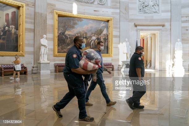 Capitol workers carry American flags through the rotunda of the U.S. Capitol in Washington, D.C., U.S., on Friday, July 30, 2021. The Senate is set...