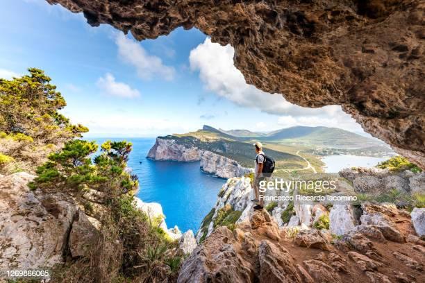 capo caccia, hiker admiring the view from a cave. sardinia, italy - cerdeña fotografías e imágenes de stock