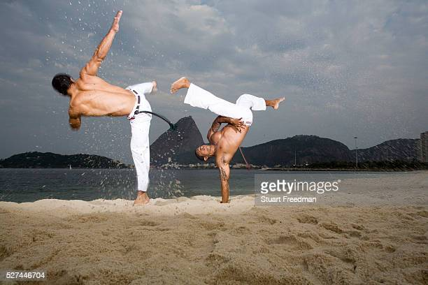 Capoeiristas practice Capoeira on Flamengo beach Capoeira is a mixture of martial arts games and dance that originated in Brazil created and...