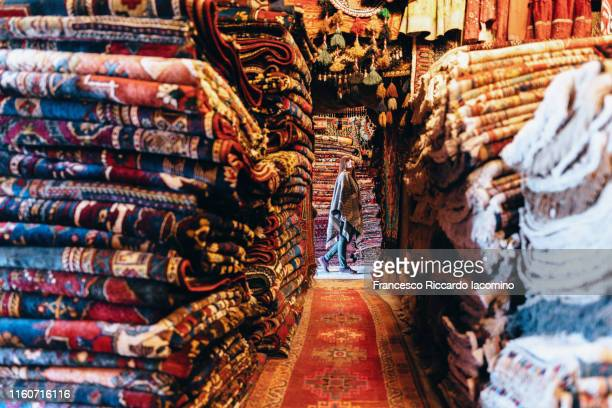 cappadocia, woman walking in a colorful carpet market. turkey - persian rug stock pictures, royalty-free photos & images