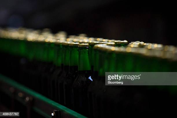 Capped bottles of Staropramen beer pass along the production line ahead of labeling at the Pivovary Staropramen AS brewing company operated by Molson...