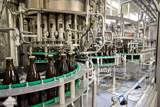 Capped brown bottles of beer pass along the production line at the Paulaner Brauerei GmbH brewery in Munich Germany on Monday Aug 18 2014 Though...