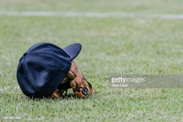 cappello e guanto da baseball su campo da gioco - silvia casali stock pictures, royalty-free photos & images