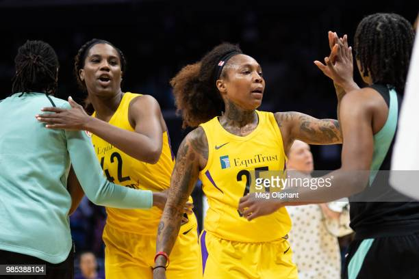 Cappie Pondexter and Jantel Lavender of the Los Angeles Sparks exchange highfives with the members of the New York Liberty after winning the game...