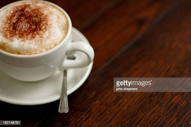 Cappuccino cup on dark wood table with copyspace
