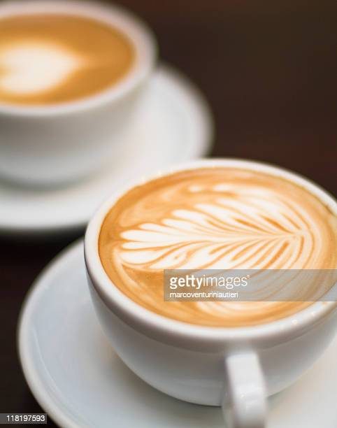 Cappuccino - One cup with decorated foam and bokeh background