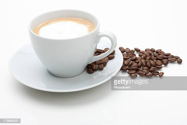 Cappuccino with fresh coffee beans in white background