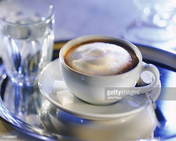 Cappuccino with glass of water on tray