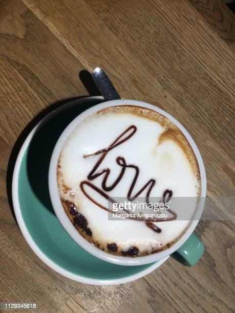 Cappuccino with 'love' written with chocolate syrup on the foam