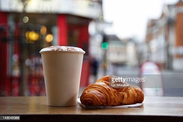 Cappucino and croissant in cafe, close-up