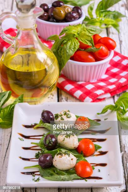 Caprese Salad with olive oil and balsamic vinegar on a white plate and a rustic wooden table