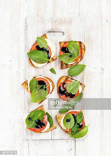 Caprese sandwiches with tomato, mozzarella cheese, basil and balsamic glaze on white painted wooden background