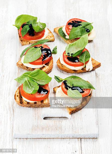 Caprese sandwiches with tomato, mozzarella cheese, basil and balsamic glaze on white painted board over light wooden background