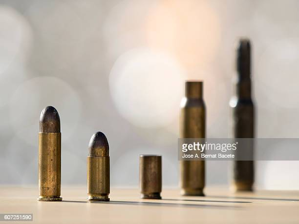 caps and bullets of a weapon of war illuminated by the light of the sun - bullet stock photos and pictures