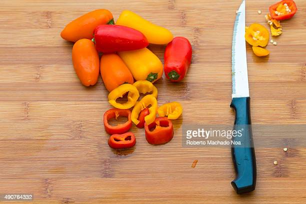 Capsicums in orange yellow and red colours on a wooden chopping board with a knife There are few uncut capsicums and some horizontally cut slices to...