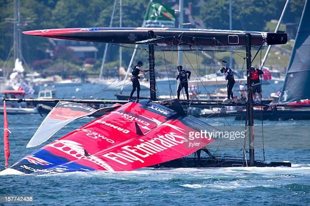 capsized catamaran racing yacht - catamaran race stock photos and pictures