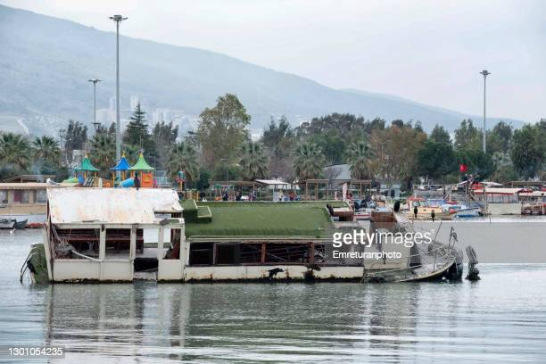 capsized tourboat inside the marina in izmir. - emreturanphoto stock pictures, royalty-free photos & images