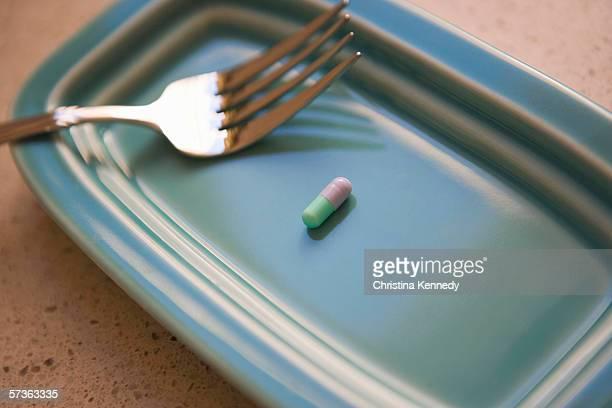 capsule and fork on plate - christina plate foto e immagini stock