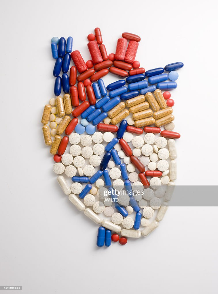 Capsules and pills in shape of human heart : Stock Photo