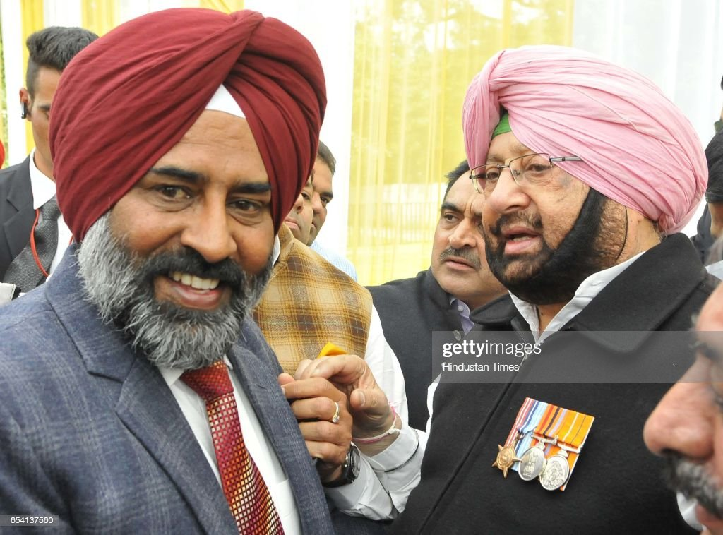 Capt Amarinder Singh and congress leader Pargat Singh interacting after oath ceremony at Punjab Raj Bhawan on March 16 2017 in Chandigarh India