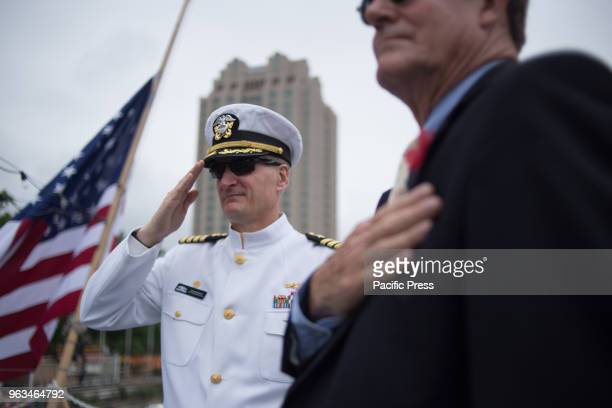 Capt Francis Spencer salutes while 'Taps' is played during the Memorial Day ceremony on board the retired USS Olympia which carried home the remains...