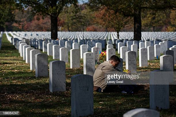 Capt Jeff Cliffe with the US Marine Corps sits next to the grave of his grandfather and grandmother on Veteran's Day at Arlington National Cemetery...