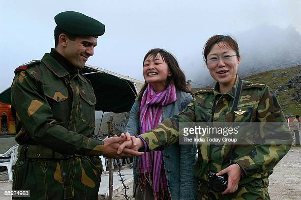 Capt Neetesh Sharma of the Indian army shakes hands with a reporter from the newspaper of the Peoples Liberation Army across the border fence at...