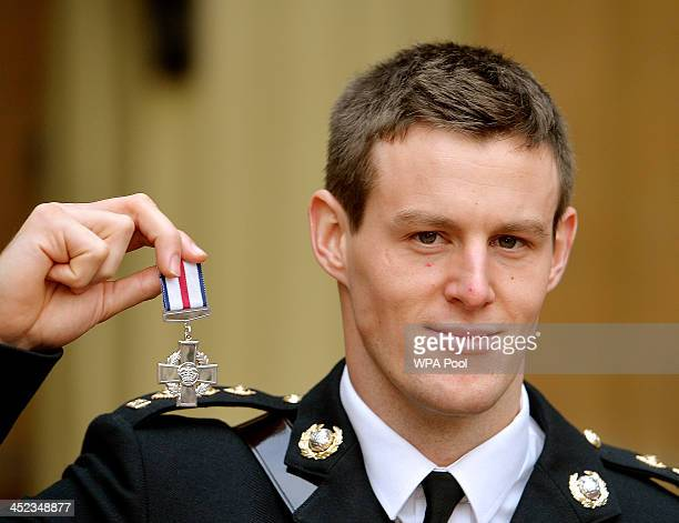 Capt Owen Davis of the Royal Marines holds his Conspicuous Gallantry Cross medal after it was presented to her by Queen Elizabeth II during the...