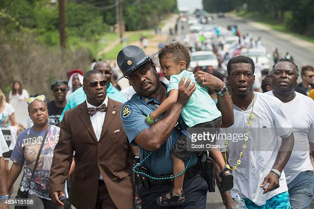 Capt Ron Johnson of the Missouri Highway Patrol carries Quinn Edwards to help out Quinn's father Franky during a nearly 5 mile march to mark the...