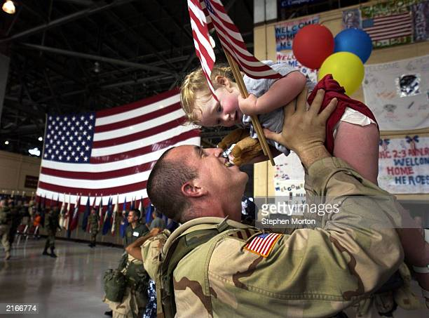 Capt. Tory Burgess, of the U.S. Army's 4th Brigade, kisses his 1-year-old daughter Dacey Wednesday July 16, 2003 in a hanger at Hunter Army Airfield...