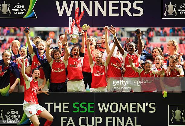 Captain Alex Scott of Arsenal lifts the trophy with team mates as they celebrate victory after the SSE Women's FA Cup Final between Arsenal Ladies...