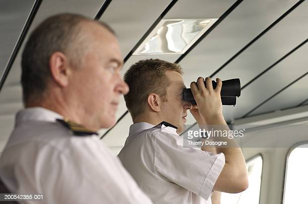 Captain and Commander on bridge of ship, one using binoculars