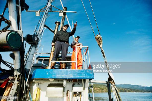 captain and crew member of fishing boat in discussion while fishing for salmon - team captain stock pictures, royalty-free photos & images