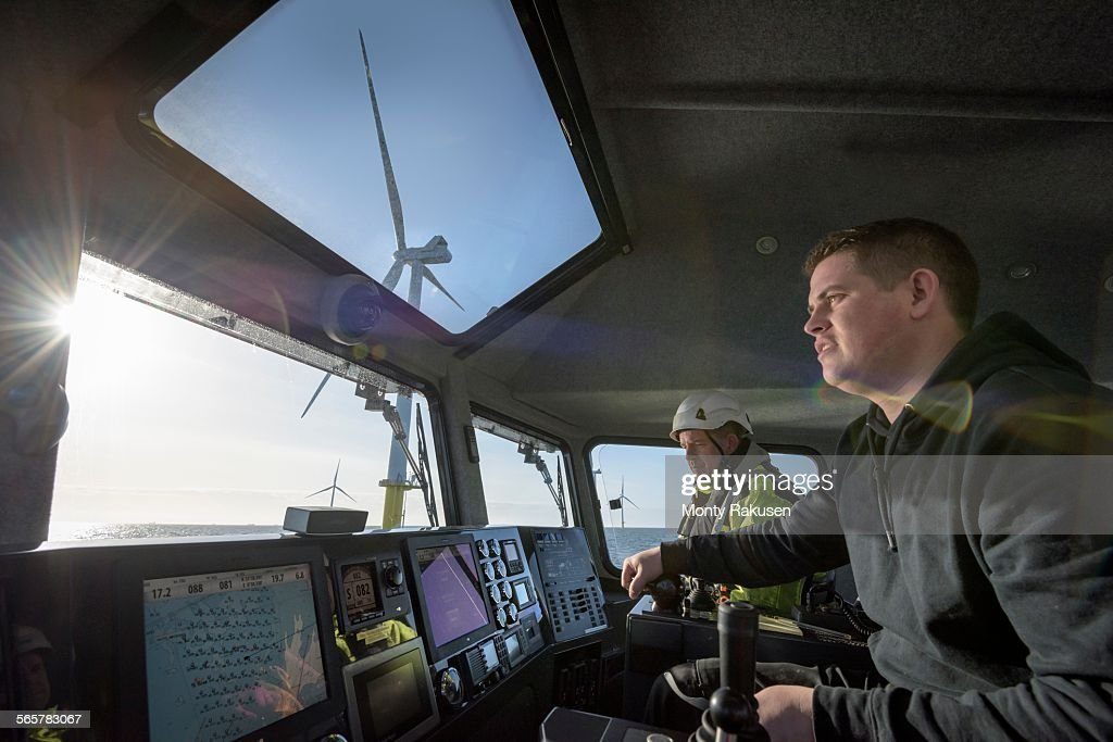 Captain and mate steer boat through offshore wind farm : Stock Photo