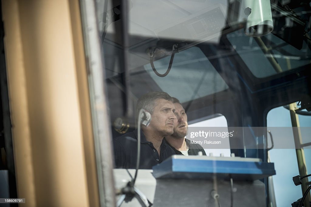 Captain and mate steering tug, view through window : Stock Photo