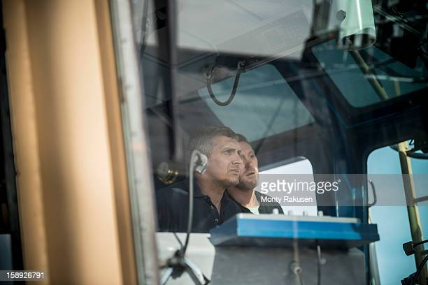 captain and mate steering tug, view through window - team captain stock pictures, royalty-free photos & images