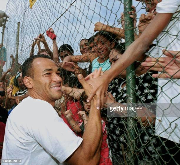 Captain and player for the Brazilian National Soccer team, Cafu, is greeted by residents of the Jardim Irene neighborhood where he was born and...
