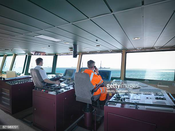 captain and worker on bridge steering ship at sea - team captain stock pictures, royalty-free photos & images