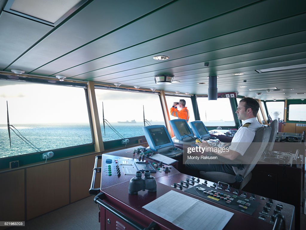 Captain and worker on bridge steering ship at sea : Stock Photo
