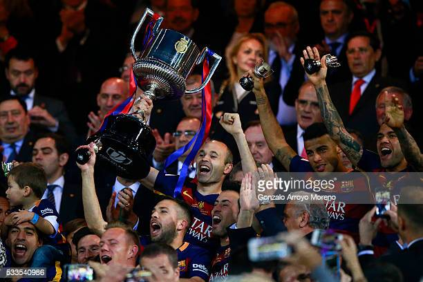 captain Andres Iniesta of FC Barcelona holds the trophy in celebration ahead King Felipe VI of Spain during the Copa del Rey Final match between FC...