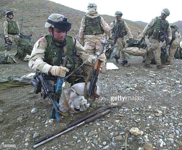 S Captain Andrew Zieseniss from St Louis Missouri inspects seized rifles from Afghan villagers during search operations around the central part of...