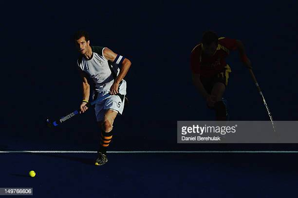 Captain Austin Smith of South Africa advances the ball forward with Roc Oliva of Spain in pursuit during the Men's Hockey match between South Africa...