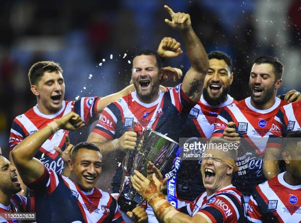 Captain Boyd Cordner of Sydney Roosters holds the trophy in victory with team mates after the World Club Challenge match between Wigan Warriors and...