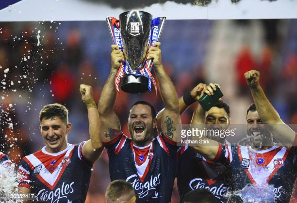 Captain Boyd Cordner of Sydney Roosters lifts the trophy in victory with team mates after the World Club Challenge match between Wigan Warriors and...